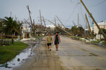 People walk through a neighborhood damaged by Hurricane Ida, Monday, Sept. 6, 2021, in Grand Isle, La. (AP Photo/John Locher)