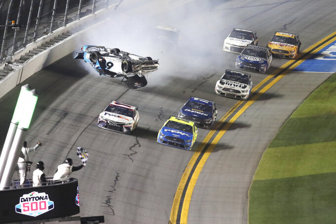 Denny Hamlin, front left, passes Ryan Blaney, front right on the way to the finish line to win NASCAR Daytona 500 auto race as Ryan Newman (6) goes upside down during a crash at Daytona International Speedway, Monday, Feb. 17, 2020, in Daytona Beach, Fla. Sunday's race was postponed because of rain. (AP Photo/David Graham)