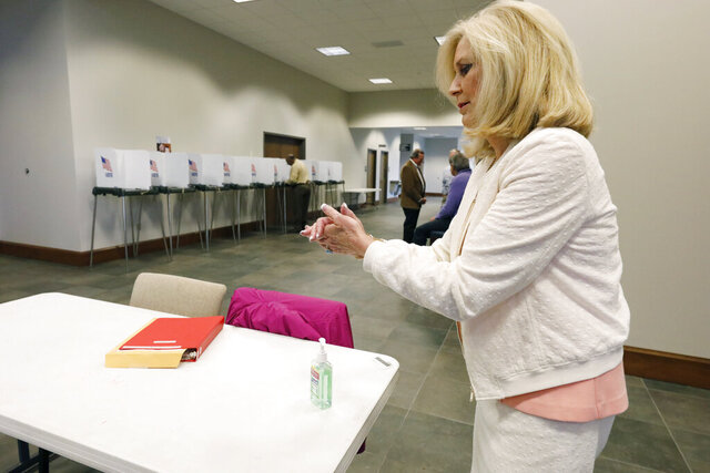 Republican Attorney General Lynn Fitch, rubs hand sanitizer on her hands after voting in the party presidential primary in Ridgeland, Miss., Tuesday, March 10, 2020. Polling locations are providing hand sanitizers for voters to use as a cautionary measure in light of the coronavirus health concern nationwide. (AP Photo/Rogelio V. Solis)