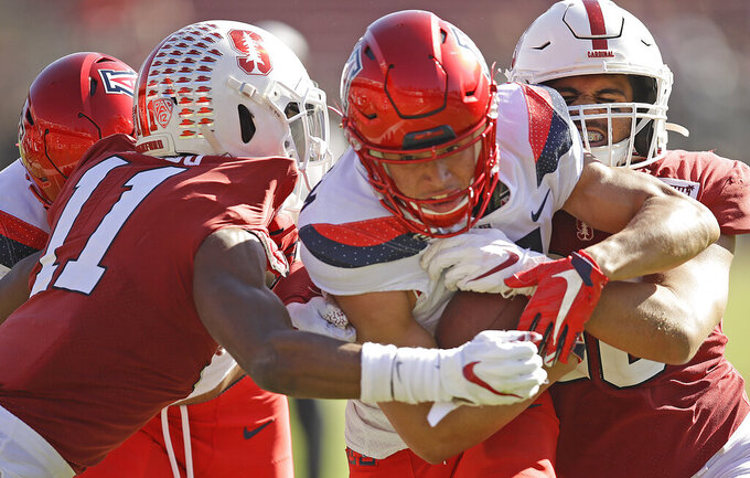 Arizona's Tayvian Cunningham, center, is tackled by Stanford's Paulson Adebo (11) in the second half of an NCAA college football game Saturday, Oct. 26, 2019, in Stanford, Calif. (AP Photo/Ben Margot)