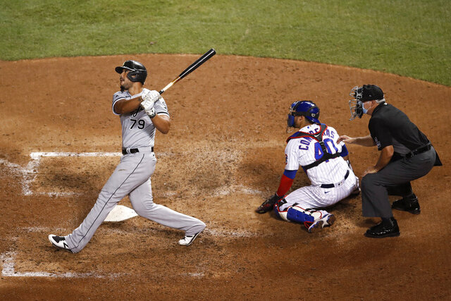 Chicago White Sox's Jose Abreu watches his two-run home run next to Chicago Cubs catcher Willson Contreras and umpire Tim Timmons during the eighth inning of a baseball game Saturday, Aug. 22, 2020, in Chicago. (AP Photo/Jeff Haynes)