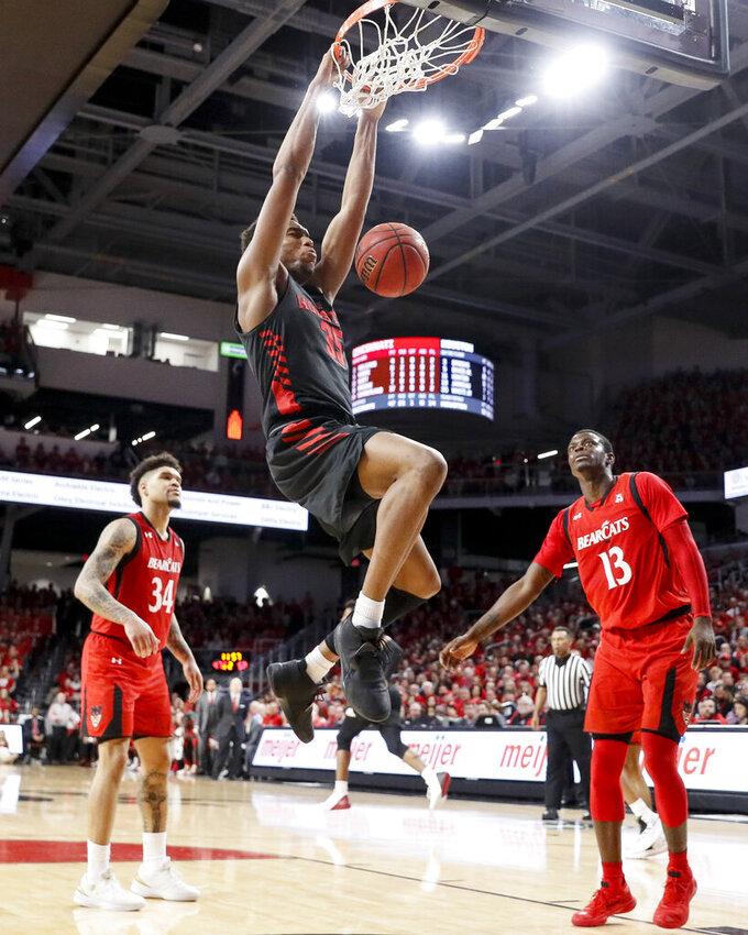 Houston's Fabian White Jr. (35) dunks as Cincinnati's Tre Scott (13) and Jarron Cumberland (34) watch in the second half of an NCAA college basketball game, Sunday, March 10, 2019, in Cincinnati. (AP Photo/John Minchillo)