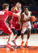 Illinois guard Ayo Dosunmu (11) moves the ball under pressure from Wisconsin guard Kobe King (23) and forward Nate Reuvers (35) during the first half of an NCAA college basketball game in Champaign, Ill., Wednesday, Jan. 23, 2019. (AP Photo/Stephen Haas)