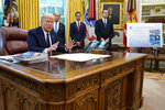 """FILE - In this Thursday, May 28, 2020 file photo, President Donald Trump speaks as he receives a briefing on the 2020 hurricane season in the Oval Office of the White House in Washington. Watching are Commerce Secretary Wilbur Ross and Neil Jacobs, assistant Secretary of Commerce for Environmental Observation and Prediction, and Pete Gaynor, administrator of the Federal Emergency Management Agency. A report from the National Academy of Public Administration released on Monday, June 15, 2020 says that NOAA's acting chief Jacobs and its then-communications director, Julie Kay Roberts, twice breached the agency's rules designed to protect scientists and their work from political interference, putting out a press statement that """"did not follow NOAA's normal proves and appear to be the result of strong external pressure."""" (AP Photo/Evan Vucci)"""