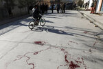 Blood stains the ground at the scene where gunmen fired in Kabul, Afghanistan, Sunday, Jan. 17, 2021. Gunmen fired on a car in northern Kabul on Sunday, killing two women judges who worked for Afghanistan's high court and wounding the driver, a court official said. It was the latest attack in the Afghan capital during peace talks between Taliban and Afghan government officials in Qatar. (AP Photo/Rahmat Gul)