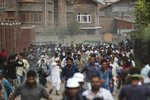FILE- In this Aug. 30, 2019, file photo, Kashmiris protesting against Indian government stripping the Himalayan state's semi-autonomous powers run for cover as Indian police use tear gas and pellets to disperse them in Srinagar, Indian controlled Kashmir. A year after India ended disputed Kashmir's semi-autonomous status and downgraded it to a federally governed territory, authorities have begun issuing residency and land ownership rights to outsiders for the first time in almost a century. Many Kashmiris view the move as the beginning of settler colonialism aimed at engineering a demographic change in India's only Muslim-majority region. (AP Photo/Mukhtar Khan, File)