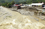 A collapsed retaining wall sits along the banks of a flooded river in Dili, East Timor, Tuesday, April 6, 2021. Several disasters brought on by severe weather in eastern Indonesia and neighboring East Timor have left a number of people dead or missing. (AP Photo/Kandhi Barnez)