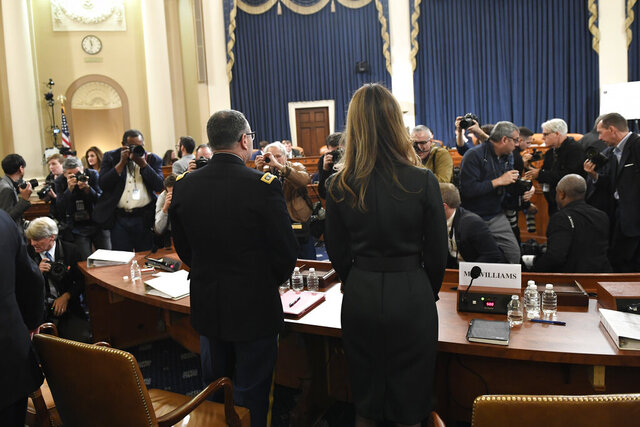 Jennifer Williams, right, an aide to Vice President Mike Pence, and National Security Council aide Lt. Col. Alexander Vindman, stand to take a break as they testify before the House Intelligence Committee on Capitol Hill in Washington, Tuesday, Nov. 19, 2019, during a public impeachment hearing of President Donald Trump's efforts to tie U.S. aid for Ukraine to investigations of his political opponents. (AP Photo/Susan Walsh)