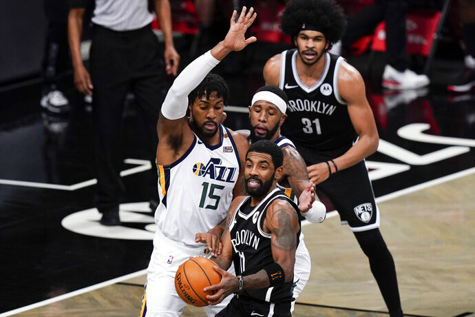 Utah Jazz's Derrick Favors (15) defens Brooklyn Nets' Kyrie Irving (11) during the second half of an NBA basketball game Tuesday, Jan. 5, 2021, in New York. (AP Photo/Frank Franklin II)