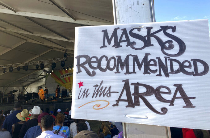In this July 31, 2021 photo, a sign recommends attendees of the Newport Jazz Festival wear masks in a tented area where singer Ledisi performs in Newport, R.I. Festival-goers were also required to digitally upload proof of COVID-19 vaccination or a recent negative test. (Matt O'Brien/AP Photo)