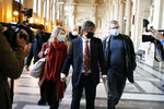 French-American Mark Moogalian, center, his wife Isabelle, left, and his lawyer Thibault de Montbrial, right, arrive at the Thalys attack trial, at the Paris courthouse, Thursday, Nov. 19, 2020. The lawyer for an American who was scheduled to testify about his role in the dramatic capture of an Islamic State operative aboard a high-speed train says his witness has been hospitalized after he flew in to Paris. (AP Photo/Francois Mori)