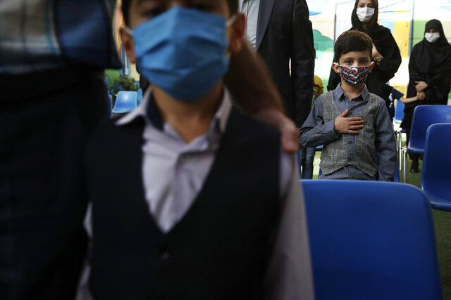 Students and their parents wearing protective face masks to help prevent spread of the coronavirus listen to their national anthem during the opening ceremony of the Hashtroudi school in Tehran, Iran, Saturday, Sept. 5, 2020. Iran on Saturday opened the new school year after nearly seven months of closure as many expressed concern over a possible increase in infections of the Covid-19. (AP Photo/Vahid Salemi)