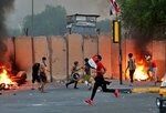 Anti-government protesters set fire while security forces fired live ammunition and tear gas near the state-run TV in Baghdad, Iraq, Monday, Nov. 4, 2019. (AP Photo/Khalid Mohammed)