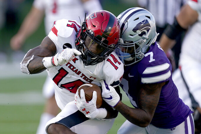 Texas Tech running back Xavier White (14) tries to get past Kansas State defensive back TJ Smith (7) during the second half of an NCAA college football game Saturday, Oct. 3, 2020, in Manhattan, Kan. (AP Photo/Charlie Riedel)