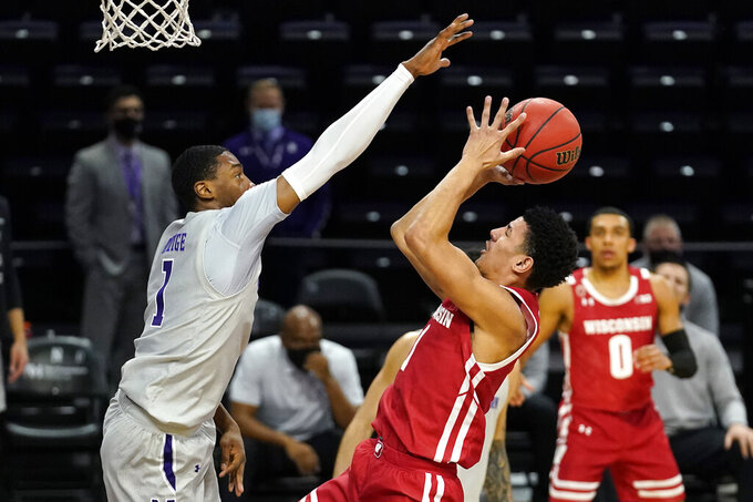 Wisconsin guard Jonathan Davis, right, shoots against Northwestern guard Chase Audige during the first half of an NCAA college basketball game in Evanston, Ill., Saturday, Feb. 21, 2021. (AP Photo/Nam Y. Huh)
