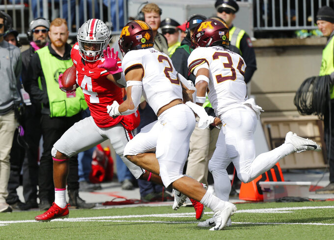 Ohio State receiver K.J. Hill, left, turns upfield against Minnesota defensive backs Jacob Huff, center, and Antonio Shenault during the first half of an NCAA college football game Saturday, Oct. 13, 2018, in Columbus, Ohio. (AP Photo/Jay LaPrete)