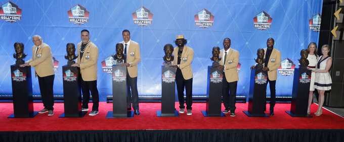 FILE - In this Aug. 4, 2019, file photo, NFL inductees and family members pose with busts during induction ceremonies at the Pro Football Hall of Fame in Canton, Ohio. From left are Gil Brandt, Kevin Mawae, Tony Gonzalez, Ed Reed, Ty Law, Champ Bailey and Pat Bowlen's family. The NFL has canceled the Hall of Fame game that traditionally opens the preseason and is delaying the 2020 induction ceremonies because of the coronavirus pandemic, two people with direct knowledge of the decision told The Associated Press on Thursday, June 25, 2020. The people spoke to the AP on condition of anonymity because the decision has not been publicly announced, though an announcement is expected later Thursday. (AP Photo/Ron Schwane, FIle)