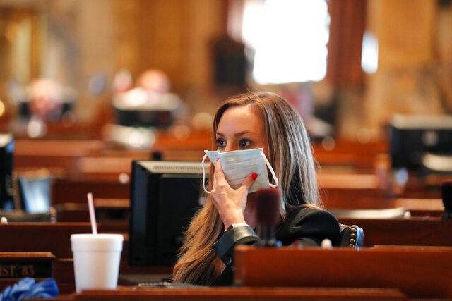 State Rep. Paula Davis, R-Dist. 69, holds a mask to her face as legislators convene in a limited number while exercising social distancing, due to the new coronavirus pandemic, at the State Capitol in Baton Rouge, La., Tuesday, March 31, 2020. They assembled briefly on the last day bills cold be introduced during the legislative session. (AP Photo/Gerald Herbert)