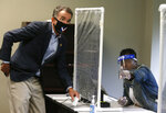 Virginia Gov. Ralph Northam, left, is shown by a poll worker which way to go as he votes early at the Richmond general registrar's office in Richmond, Va., Friday, Sept. 18, 2020, on the first day of Virginia's 45-day early voting period. (Bob Brown/Richmond Times-Dispatch via AP)
