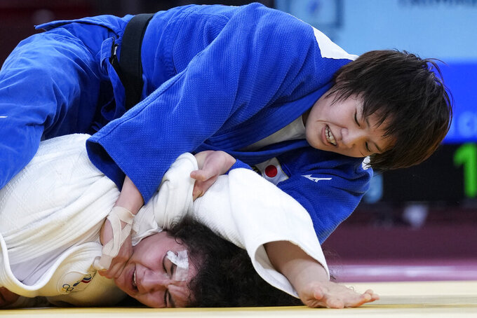 Madina Taimazova of Russian Olympic Committee, bottom, and Chizuru Arai of Japan compete in the women -70kg semifinal round of the judo match at the 2020 Summer Olympics in Tokyo, Japan, Wednesday, July 28, 2021. (AP Photo/Vincent Thian)