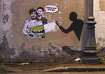 """FILE - In this Feb. 19, 2020 file photo, a mural depicting detained Egyptian human rights advocate and student at the University of Bologna in Italy Patrick George Zaki, being hugged from behind by Italian researcher Giulio Regeni, who was murdered in Cairo in 2016, is displayed on a wall in Rome. The trial of Zaki who has been imprisoned for over a year in Egypt began Tuesday, Sept. 14, 2021 amid calls by human rights advocates for his immediate release, his lawyers said. Zaki appeared before a State Security Misdemeanors Court in the Delta town of Mansoura to face charges of spreading false news  about Egypt domestically and abroad. Writing in Italian at top reads: """"This time it will all go well"""", and in Arabic at the bottom reads """"freedom."""" (AP Photo/Gregorio Borgia, File)"""