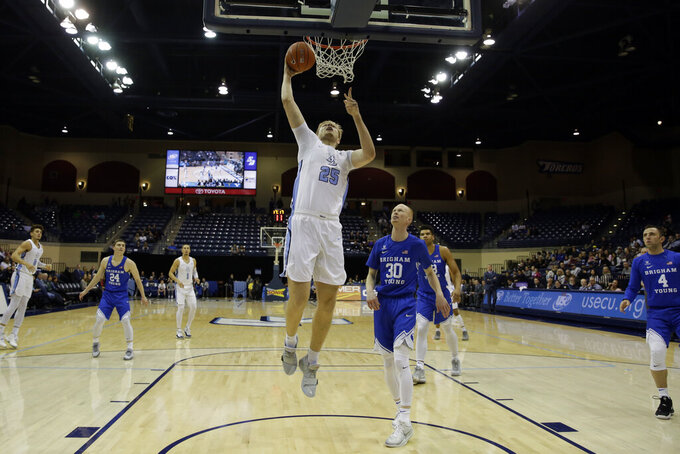 San Diego forward Yauhen Massalski, center, shoots over Brigham Young guard TJ Haws during the first half of an NCAA college basketball game Thursday, Feb. 14, 2019, in San Diego. (AP Photo/Gregory Bull)