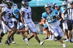 Carolina Panthers running back Christian McCaffrey, right, runs past Baltimore Ravens safety DeShon Elliott (32), far left, and cornerback Anthony Averett (23) during a joint practice hosted by Carolina at the NFL football team's training camp in Spartanburg, S.C., Thursday, Aug. 19, 2021. (AP Photo/Nell Redmond)