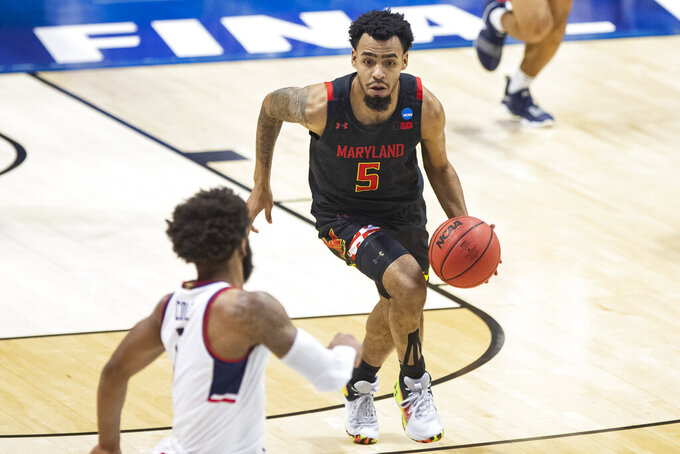 Maryland's Eric Ayala (5) brings the ball up as Connecticut's R.J. Cole defends during the first half of a first-round game in the NCAA men's college basketball tournament Saturday, March 20, 2021, at Mackey Arena in West Lafayette, Ind. (AP Photo/Robert Franklin)