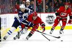 Winnipeg Jets' Mason Appleton (82) battles for the puck with Carolina Hurricanes' Haydn Fleury (4) during the first period of an NHL hockey game in Raleigh, N.C., Tuesday, Jan. 21, 2020. (AP Photo/Karl B DeBlaker)