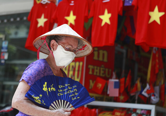 A woman walks past a row of T-shirts printed with Vietnamese flags in Hanoi, Vietnam on Thursday, Jul.30, 2020. For 99 days, Vietnam seemed to have defeated the coronavirus, but now a new outbreak in the city of Da Nang has grown to over 40 cases in six cities and authorities are beginning to reimpose broader restrictions. (AP Photo/Hau Dinh)