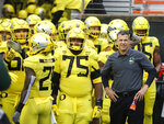 FILE - In this Nov. 23, 2018, file photo, Oregon coach Mario Cristobal stands with players before the team's NCAA college football game against Oregon State in Corvallis, Ore. The Ducks are the highest-ranked Pac-12 team and the North Division favorite. They go into Saturday night's game against Auburn, the opener of Cristobal's second season, with a three-game winning streak after a 9-4 season. (AP Photo/Timothy J. Gonzalez, File)