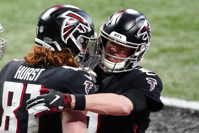 Atlanta Falcons quarterback Matt Ryan (2) embraces Atlanta Falcons tight end Hayden Hurst (81) after hurst scored a touchdown during the second half of an NFL football game, Sunday, Dec. 20, 2020, in Atlanta. (AP Photo/Brynn Anderson)