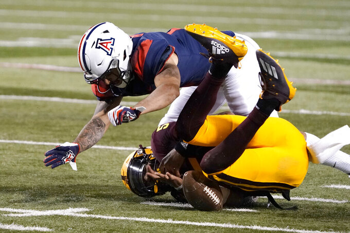 Arizona State quarterback Jayden Daniels, bottom, recovers a fumble next to Arizona defensive back Lorenzo Burns during the first half of an NCAA college football game Friday, Dec. 11, 2020, in Tucson, Ariz. (AP Photo/Rick Scuteri)