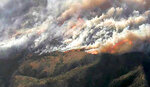 In this image from video provided by KNBC-TV, smoke and flames from the Silverado fire threatens areas near Irvine, Calif., Monday, Oct. 26, 2020. The fast-moving wildfire has forced evacuations for 60,000 people in Southern California as powerful winds across the state prompted power to be cut to hundreds of thousands to prevent utility equipment from sparking new blazes. (KNBC-TV via AP