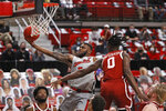Texas Tech's Jamarius Burton (2) lays up the ball around Oklahoma's Victor Iwuakor (0) during the second half of an NCAA college basketball game Monday, Feb. 1, 2021, in Lubbock, Texas. (AP Photo/Brad Tollefson)
