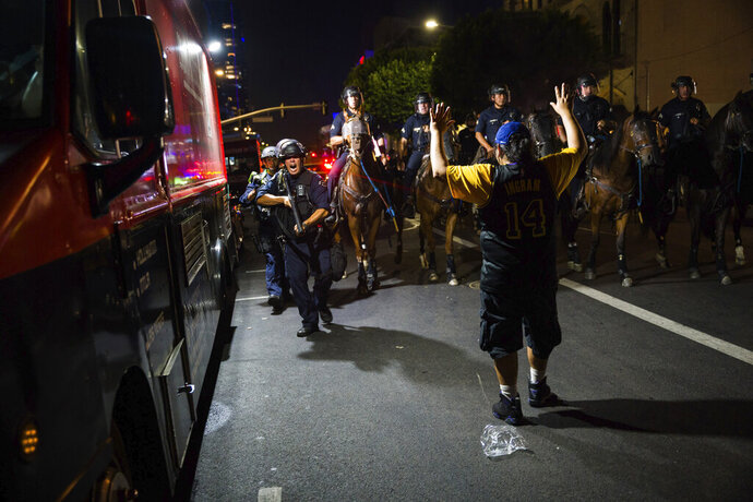 Los Angeles Police Department officers on horseback move people back as rowdy fans celebrate, Sunday, Oct. 11, 2020, in Los Angeles, after the Los Angeles Lakers defeated the Miami Heat in Game 6 of basketball's NBA Finals to win the championship. (AP Photo/Jintak Han)