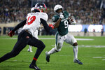 Michigan State's Kenneth Walker III, right, runs for a touchdown against Western Kentucky's Miguel Edwards during the first quarter of an NCAA college football game, Saturday, Oct. 2, 2021, in East Lansing, Mich. (AP Photo/Al Goldis)