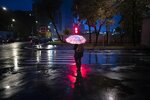 A pedestrian holds an umbrella as he waits for a green traffic light on an almost empty street during an autumn rain in Moscow, Russia, Tuesday, Sept. 21, 2021. The temperature in Moscow dropped to about 7 degrees (44,6 degrees Fahrenheit). (AP Photo/Alexander Zemlianichenko)