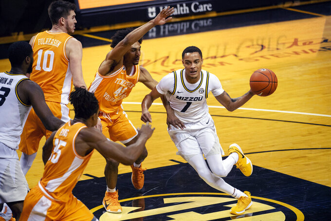 Missouri's Xavier Pinson, right, passes the ball past Tennessee's Keon Johnson, center, during the second half of an NCAA college basketball game Wednesday, Dec. 30, 2020, in Columbia, Mo. (AP Photo/L.G. Patterson)