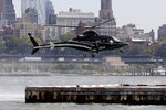 In this Wednesday, Oct. 2, 2019, photo an Uber helicopter lands at the Downtown Manhattan Heliport, in New York. The ride-hailing company expanded its helicopter service Thursday, Oct. 3, between lower Manhattan in New York City and John F. Kennedy International Airport, making it available to all Uber riders with iPhones instead of just those in the top tiers of its rewards program. (AP Photo/Richard Drew)