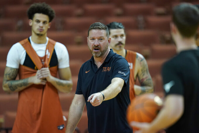 In this Tuesday, Oct. 19, 2021, photo, Texas head coach Chris Beard, center, directs a practice at the team's facility, in Austin, Texas. Beard starts his season with the Longhorns with a roster loaded with transfers who collectively bring more than 750 games and nearly 8,000 points and 3,000 rebounds in their new program. (AP Photo/Eric Gay)