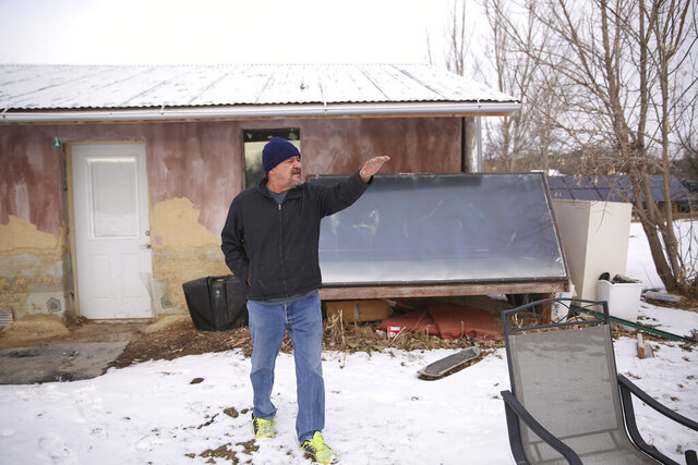 In this Dec. 11, 2019 photo, Henry Red Cloud stands outside the workshop where he teaches renewable energy installation on Pine Ridge Indian Reservation in South Dakota. A variety of green energy projects are sprouting up on American Indian reservations. Some tribes are looking to make money and others just want to benefit the community with reduced energy bills and green jobs. The Standing Rock tribe in North Dakota recently built a small solar farm near the site of long and tumultuous protests over the Dakota Access pipeline.(AP Photo/Stephen Groves)