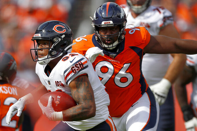 FILE - In this Sept. 15, 2019, file photo, Chicago Bears running back David Montgomery (32) is pursued by Denver Broncos defensive tackle Shelby Harris (96) during the first half of an NFL football game in Denver. The coronavirus pandemic has forced NFL teams to make free agent decisions without the benefit of meeting players face to face. That suppressed the market for plenty of lower-tier free agents such as Harris who signed a one-year deal for $2.5 million with a chance to earn another $750,000. (AP Photo/David Zalubowski, File)