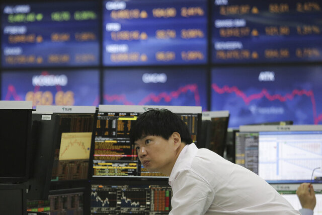 A currency trader watches monitors at the foreign exchange dealing room of the KEB Hana Bank headquarters in Seoul, South Korea, Wednesday, May 6, 2020. Asian stock markets were mixed Wednesday as hopes for a global economic recovery rose after more governments eased anti-virus controls. (AP Photo/Ahn Young-joon)