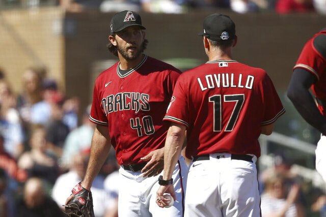 Arizona Diamondbacks starting pitcher Madison Bumgarner (40) talks with manager Torey Lovullo, right, after leaving a spring training baseball game after pitching a shutout into the fourth inning against the Kansas City Royals, Monday, March 9, 2020, in Scottsdale, Ariz. (AP Photo/Ross D. Franklin)
