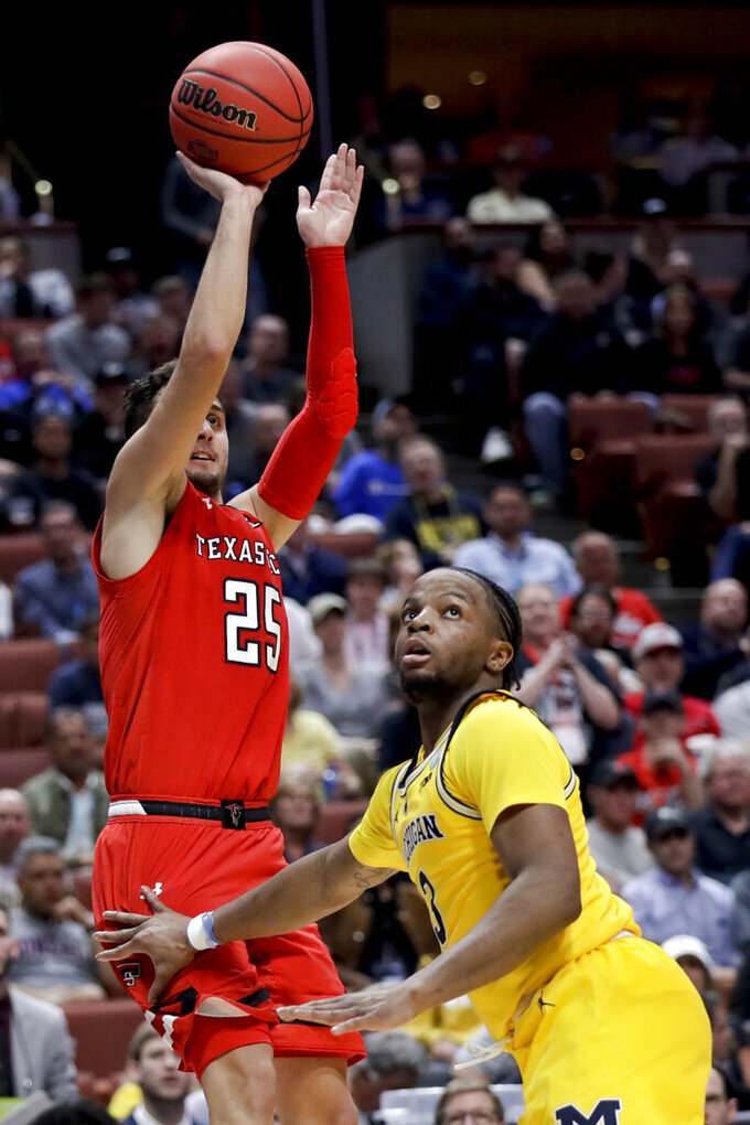 Texas Tech guard Davide Moretti shoots over Michigan guard Zavier Simpson during the second half an NCAA men's college basketball tournament West Region semifinal Thursday, March 28, 2019, in Anaheim, Calif. (AP Photo/Marcio Jose Sanchez)