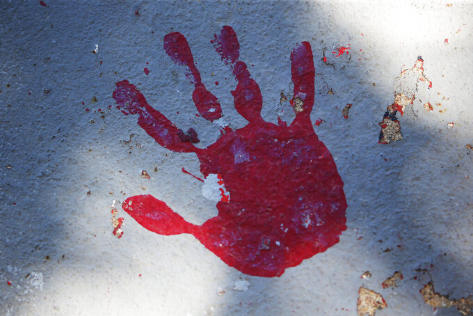 A red handprint is painted along a walkway which leads from the Bountiful High School parking lot up to the football field Tuesday, July 28, 2020, in Bountiful, Utah. While advocates have made strides in getting Native American symbols and names changed in sports, they say there's still work to do mainly at the high school level, where mascots like Braves, Indians, Warriors, Chiefs and Redskins persist. (AP Photo/Rick Bowmer)