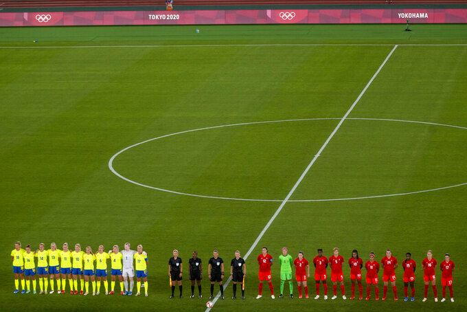 Players of Sweden, left, and Canada prior to the women's soccer match for the gold medal at the 2020 Summer Olympics, Friday, Aug. 6, 2021, in Yokohama, Japan. (AP Photo/Kiichiro Sato)