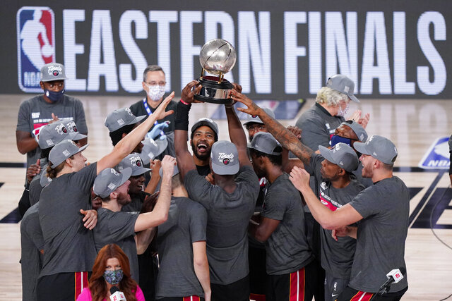 The Miami Heat celebrate their NBA conference final playoff basketball game win over the Boston Celtics with the Eastern Final trophy Sunday, Sept. 27, 2020, in Lake Buena Vista, Fla. (AP Photo/Mark J. Terrill)