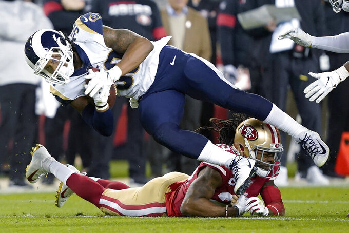 Los Angeles Rams running back Todd Gurley II (30) is tackled by San Francisco 49ers cornerback Richard Sherman, bottom, during the second half of an NFL football game in Santa Clara, Calif., Saturday, Dec. 21, 2019. (AP Photo/Tony Avelar)